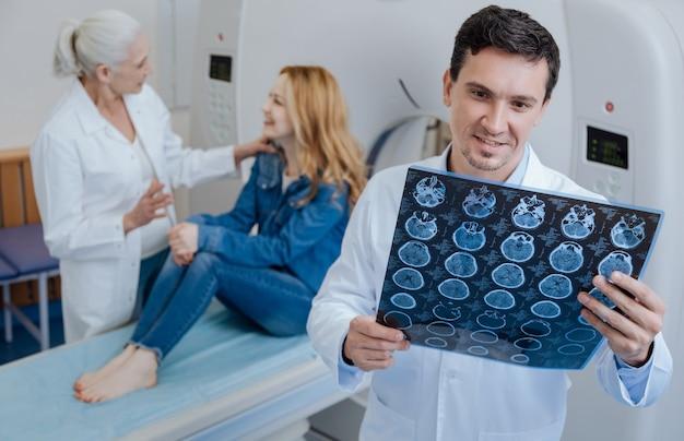 Blij positieve knappe dokter die ct-scanresultaten vasthoudt en glimlacht terwijl hij geen problemen ziet