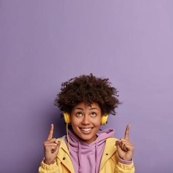 Blij positieve vrouw heeft krullend kapsel, wijst met wijsvinger naar het plafond, toont kopie ruimte hierboven, heeft een goed humeur terwijl ze grappige liedjes luistert