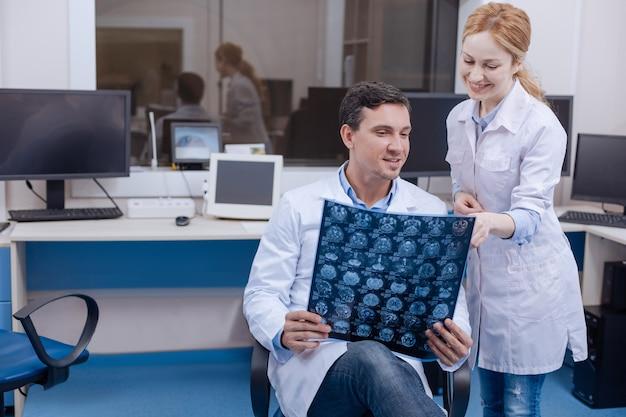 Blij positieve vrouwelijke arts die naast haar mannelijke collega stond en naar de röntgenfoto wees terwijl ze de verbetering opmerkte