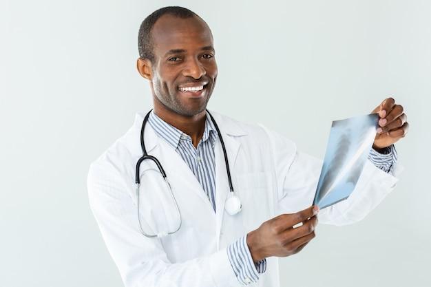 Blij professiaonl afro-amerikaanse arts die röntgenscan houdt terwijl hij bij het werk betrokken is