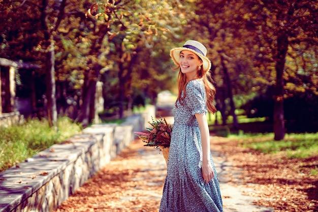 Blij roodharig meisje loopt alleen in het herfstpark op een zonnige warme dag terwijl ze in de zomer een handtas vasthoudt