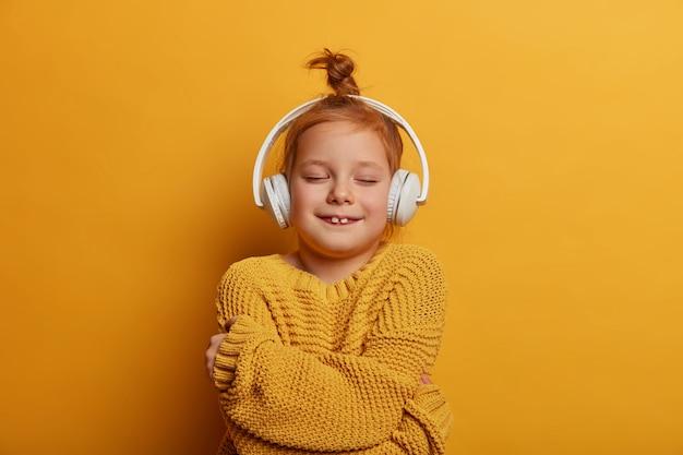 Blij roodharig meisje met haarknotje, omhelst zichzelf, voelt troost in nieuwe gebreide trui, luistert melodie in stereohoofdtelefoons, geïsoleerd over levendige gele muur. kinderen, hobby-concept
