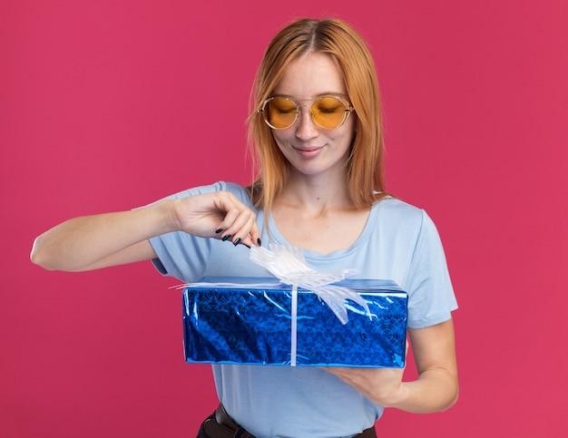 Blij roodharige gember meisje met sproeten in zonnebril houden en kijken naar geschenkdoos geïsoleerd op roze muur met kopie ruimte