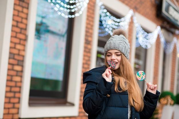 Blij roodharige jonge vrouw met grijze gebreide muts en bijt kerstsnoepjes