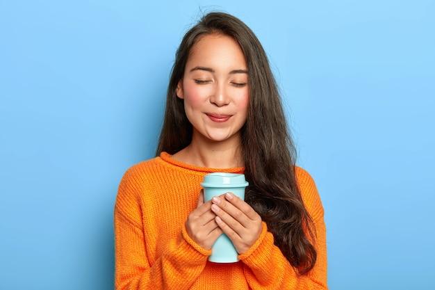 Blij rustgevend meisje met aziatische uitstraling, houdt de ogen gesloten, glimlacht zachtjes, geniet van het drinken van aromatische espresso uit afhaalbeker, draagt oranje trui