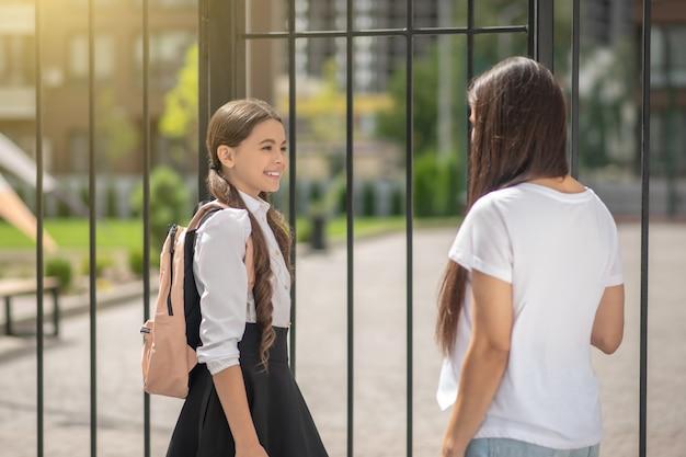Blij schattig schoolmeisje met rugzak met moeder in de buurt van schoolpoort op zonnige ochtend