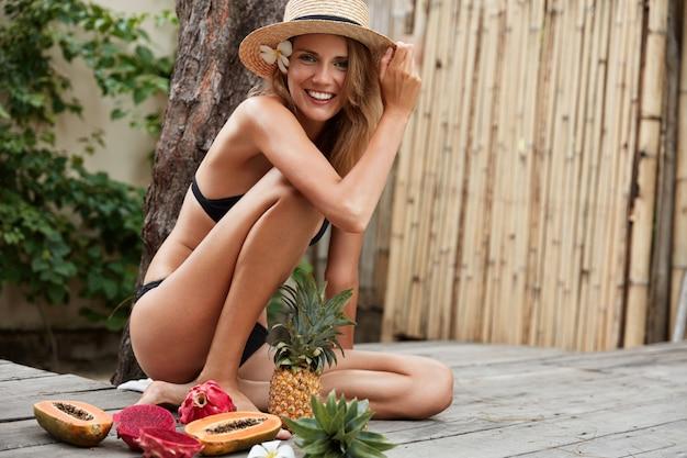 Blij schattig vrouwelijk model draagt zwarte bikini, zomerhoed, zit op houten vloer met exotisch fruit,