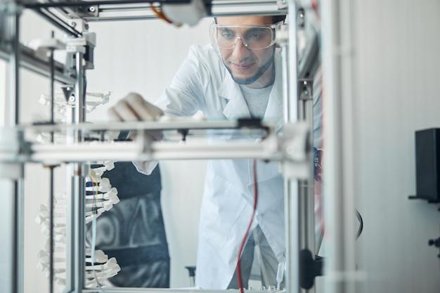 Blij schattige donkerharige jonge mannelijke ingenieur in veiligheidsbril staren naar het 3d-geprinte object