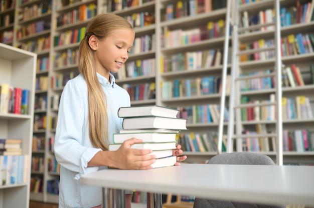 Blij scholier die schoolboeken op het bureau plaatst