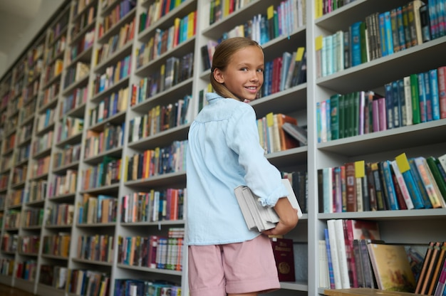 Blij schoolkind met schoolboeken die over haar schouder terugkijken
