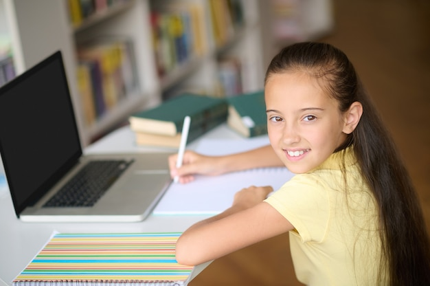 Blij schoolmeisje dat aantekeningen maakt in haar notitieboekje