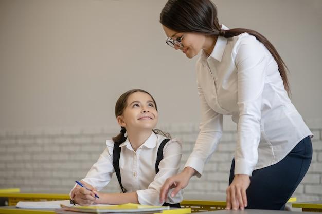 Blij schoolmeisje dat bij haar bureau glimlachende vrouwelijke leraar bekijkt die met glazen dichtbij zich bevindt