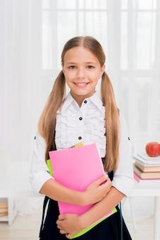 Blij schoolmeisje dat zich met heldere werkboeken bevindt