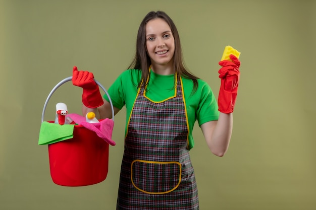 Blij schoonmakend jong meisje die uniform in rode handschoenen dragen die schoonmakende hulpmiddelen met spons op geïsoleerde groene achtergrond houden