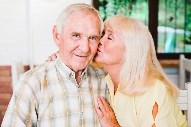 Blij senior paar knuffelen zitten in café en kussen