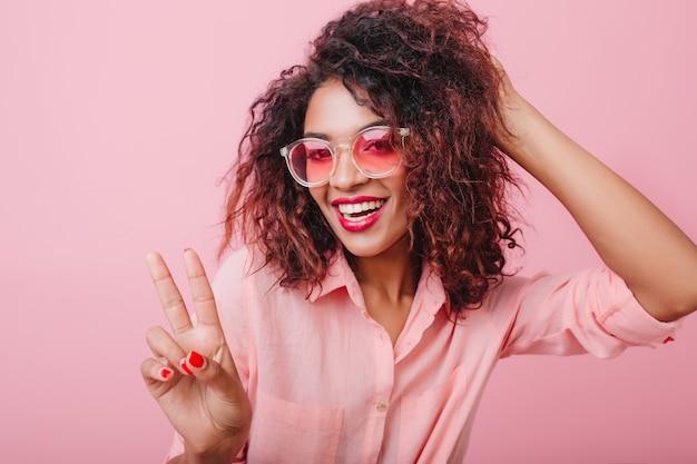 Blij sensuele mulat meisje in stijlvolle zonnebril poseren met vredesteken. elegante charmante vrouw in formele kleding met plezier.
