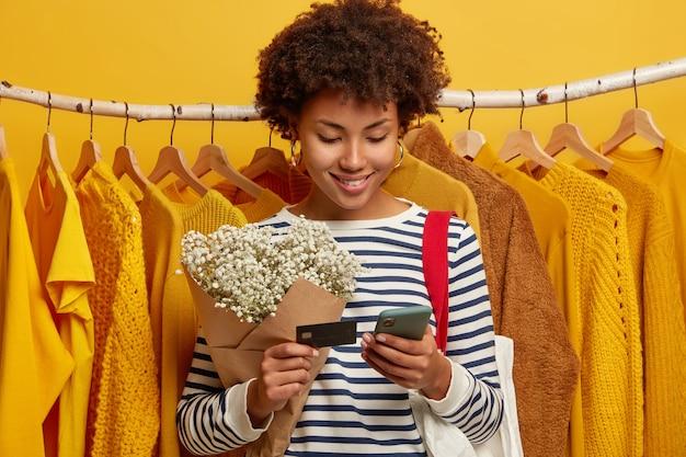 Blij shopaholic staat in de buurt van verschillende kleding aan hangers, koopt kleding online of betaalt voor aankoop met creadit-kaart en mobiele telefoonapplicatie