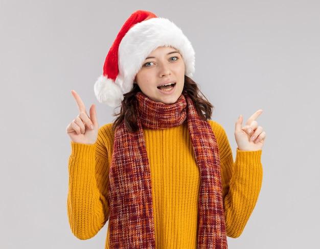 Blij slavisch meisje met kerstmuts en met sjaal om nek die omhoog wijst geïsoleerd op een witte muur met kopieerruimte