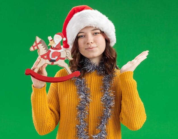 Blij slavisch meisje met kerstmuts en met slinger om de nek die de kerstman op hobbelpaarddecoratie houdt en de hand open houdt geïsoleerd op de groene muur met kopieerruimte