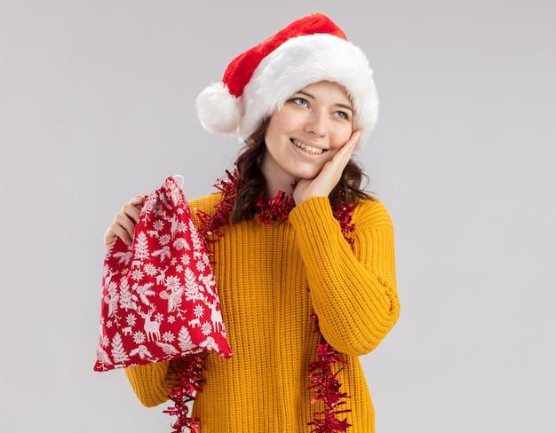 Blij slavisch meisje met kerstmuts en met slinger om nek legt hand op het gezicht en houdt kerstcadeauzakje kijkend naar kant geïsoleerd op een witte muur met kopieerruimte