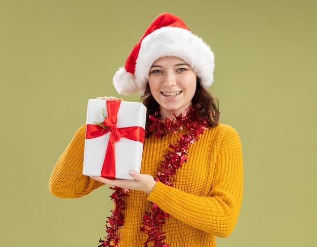 Blij slavisch meisje met kerstmuts en met slinger om nek met kerstcadeaudoos geïsoleerd op olijfgroene muur met kopieerruimte