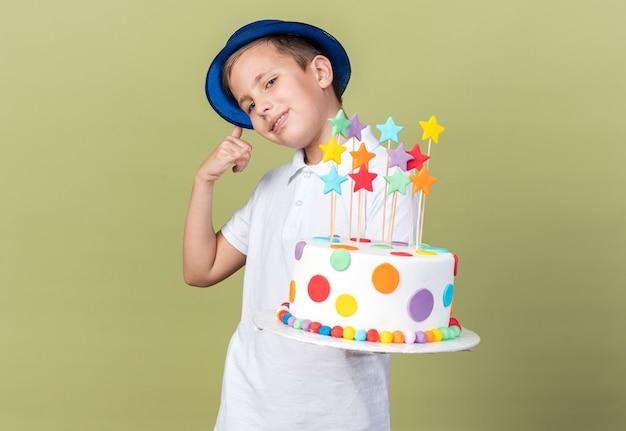 Blij slavische jongen met blauwe feestmuts met verjaardagstaart en gebaren bel me teken geïsoleerd op olijfgroene muur met kopie ruimte