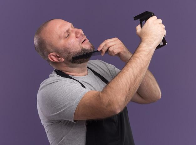 Blij slavische mannelijke kapper van middelbare leeftijd in uniform baard kammen en water geven met spuitfles geïsoleerd op paarse muur