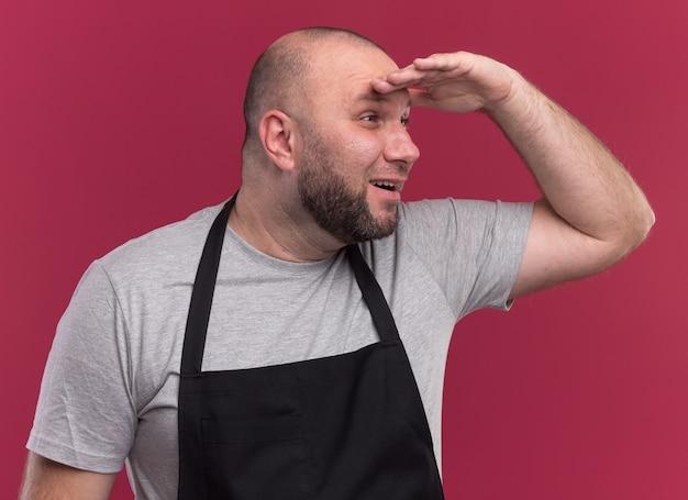 Blij slavische mannelijke kapper van middelbare leeftijd in uniform kijkend naar afstand met hand geïsoleerd op roze muur