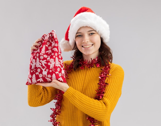 Blij slavische meisje met kerstmuts en met slinger om nek houden kerstcadeau tas geïsoleerd op een witte muur met kopie ruimte
