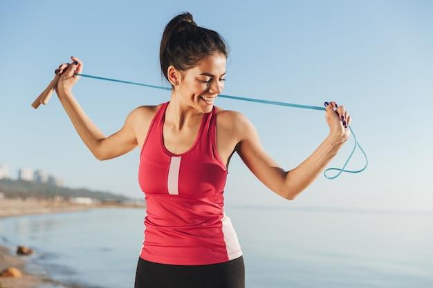 Blij sport vrouw poseren met springtouw en wegkijken