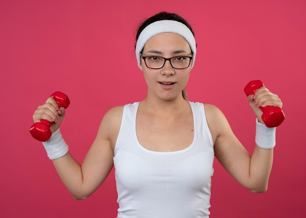 Blij sportief meisje in optische bril met hoofdband en polsbandjes met halters