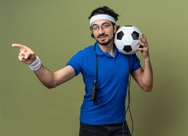 Blij sportieve jongeman met hoofdband met polsband en springtouw op schouder met balpunten aan de zijkant