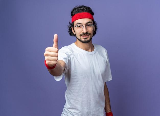 Blij sportieve jongeman met hoofdband met polsbandje duim opdagen