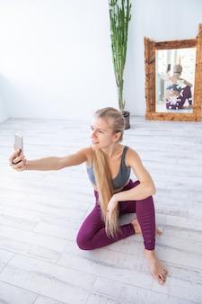 Blij sportvrouw glimlachend en selfie te nemen zittend op de vloer in de buurt van spiegel en potplant tijdens pauze in fitnesstraining thuis