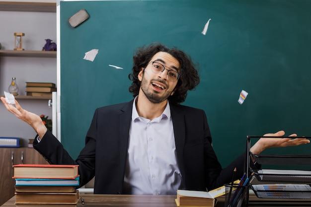 Blij spreidende handen mannelijke leraar met een bril scheurt papier omhoog zittend aan tafel met schoolgereedschap in de klas