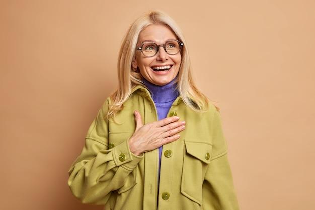 Blij, stijlvolle blonde veertigjarige vrouw, gekleed in modieuze kleding, houdt de hand op de borst en glimlacht positief als zich herinnert dat er iets grappigs met haar is gebeurd.