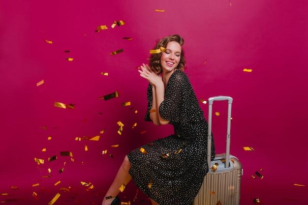 Blij stijlvolle dame dromerige poseren op paarse achtergrond voor aanstaande reis