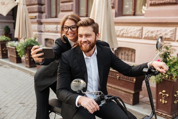 Blij stijlvolle paar zittend op moderne motor buitenshuis