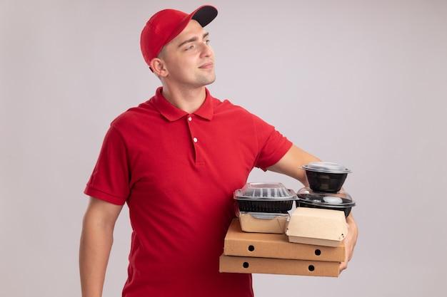 Blij te kijken naar de jonge bezorger die aan de zijkant een uniform met pet draagt en voedselcontainers op pizzadozen houdt die op een witte muur worden geïsoleerd