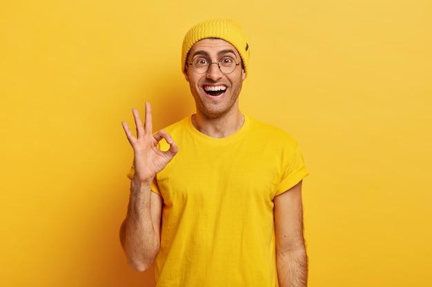 Blij tevreden man toont ok gebaar of goedkeuringsteken, geeft positief antwoord, beweert dat alles in orde is