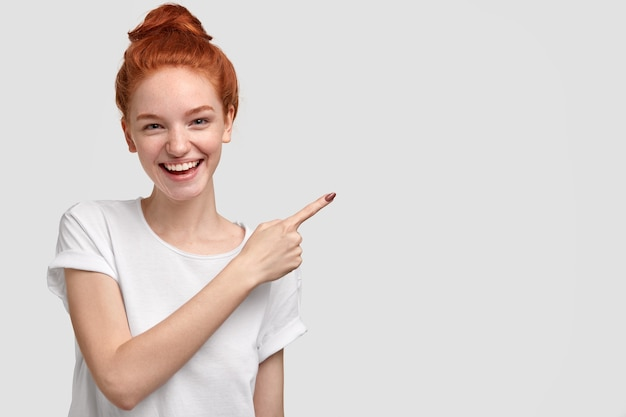 Blij tevreden roodharige jonge vrouw met charmante glimlach, toont vrije ruimte, adverteert iets