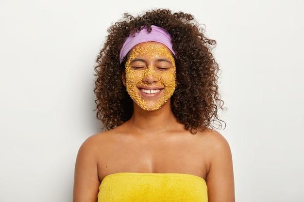 Blij tevreden vrouw met afro-kapsel maakt natuurlijke gezichtsscrub met gele zeezout, krijgt een gladdere huid, verwijdert irritatie en donkere vlekken, verbetert de mineralenbalans, heeft schoonheidsroutine, gewikkeld in een handdoek