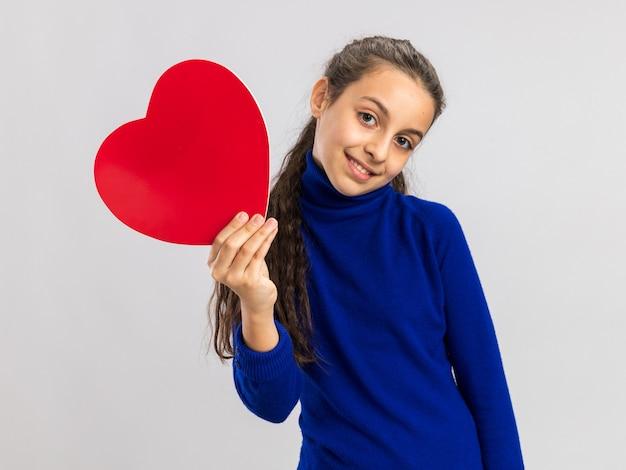 Blij tienermeisje met hartvorm kijkend naar de voorkant geïsoleerd op een witte muur