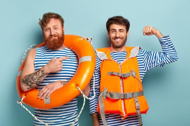Blij, trotse mannelijke zwemmer heft arm op en toont spieren, klaar om mensen het leven op water te redden