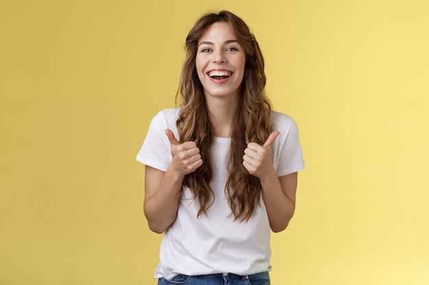 Blij uitgaande vrolijk knap kaukasisch meisje krullend lang kapsel wit t-shirt toon duimen omhoog glimlachend levendig blij als geweldige prestaties goedkeuren goede keuze gele achtergrond