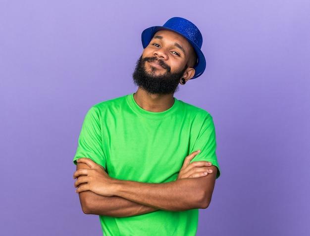 Blij uitziende camera jonge afro-amerikaanse man met feesthoed die handen kruist