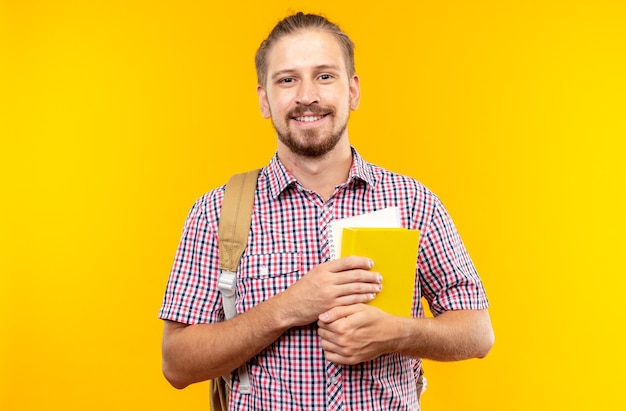 Blij uitziende camera jonge kerel student draagt rugzak met boek geïsoleerd op oranje muur