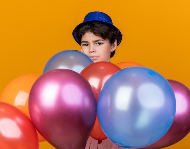 Blij uitziende camera kleine jongen met een blauwe feestmuts die achter ballonnen staat