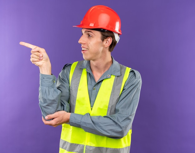 Blij uitziende jonge bouwer aan de kant in uniforme punten aan de zijkant geïsoleerd op een blauwe muur met kopieerruimte