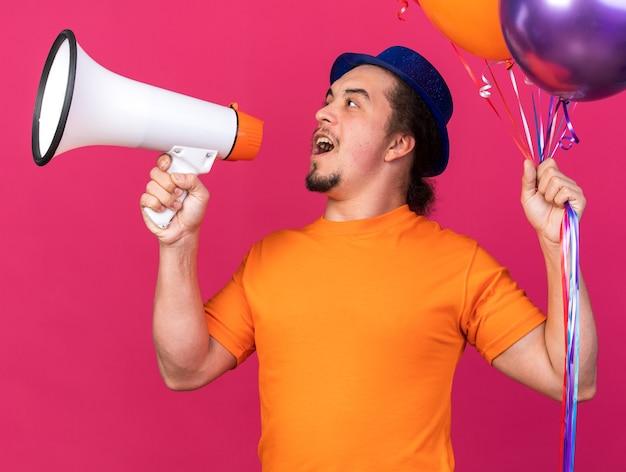 Blij uitziende jonge man met een feesthoed met ballonnen spreekt op een luidspreker die op een roze muur is geïsoleerd